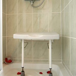 Drop down shower seat in white with legs extended