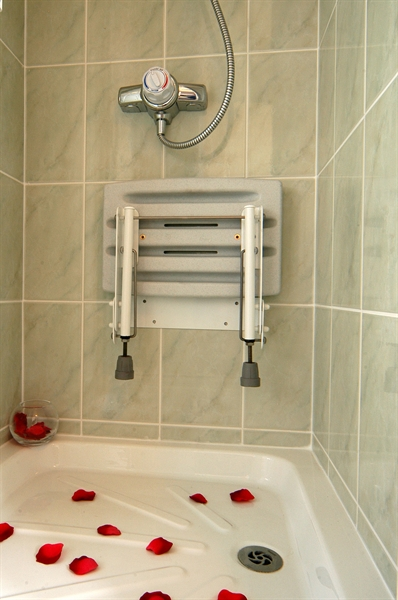 Drop down shower seat in white with legs in upright position