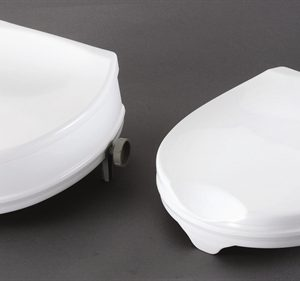two white raised toilet seats with lids